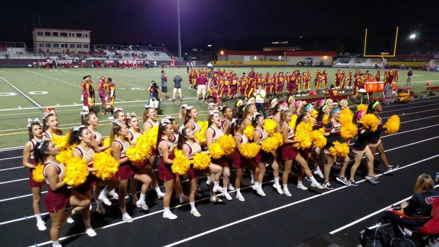 Schaumburg cheerleaders and poms perform at a home football game in front of the Saxon fans.