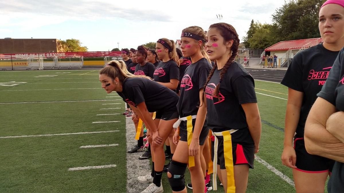 Senior powderpuff girls watch from the sidelines as the seniors defeat the juniors 30-6.