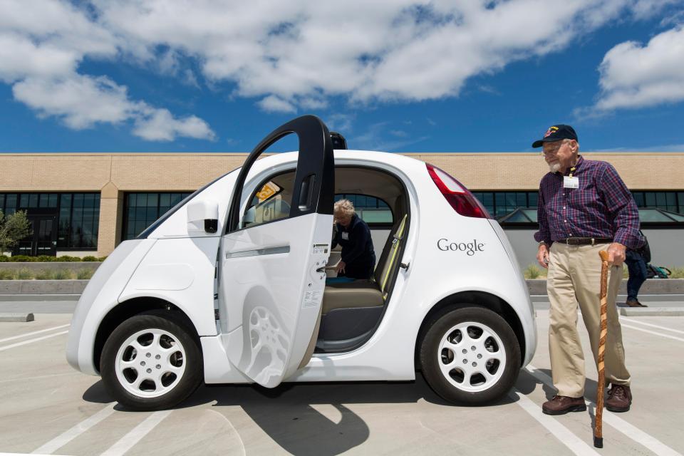 A passenger approaches a self-driving car.