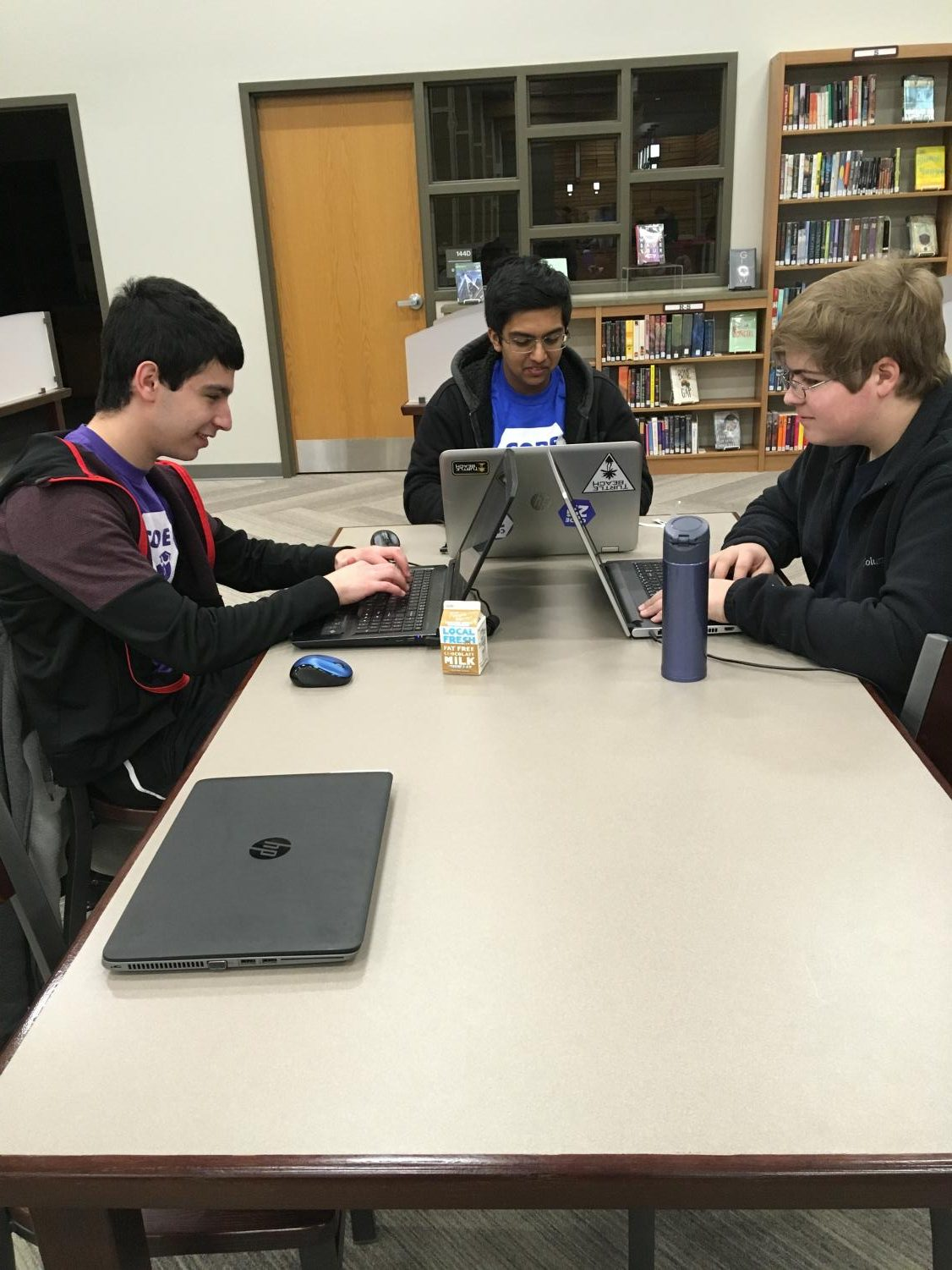 Brody Adelman, Pranay Singh, and Gavin Andres code in the Fremd Media Center during the Code211 Hackathon.