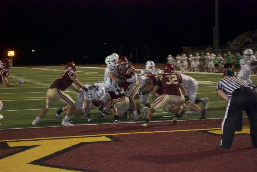 Saxons defenders attempt to keep a York ball carrier out of the end zone during a 16-13 week one  overtime loss .