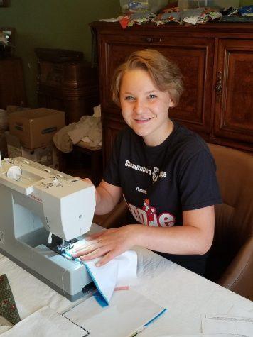 Emma Davenport stitches masks for MasksNOW, a now national organization.