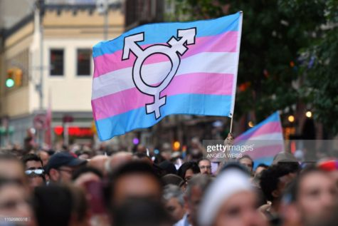 A person holds a transgender pride flag as people gather on Christopher Street outside the Stonewall Inn for a rally to mark the 50th anniversary of the Stonewall Riots in New York, June 28, 2019. - The June 1969 riots, sparked by repeated police raids on the Stonewall Inn -- a well-known gay bar in New York